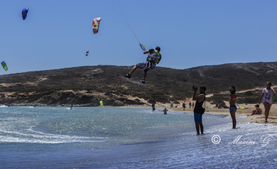 kiting towards the beach, flying above white sand, canon